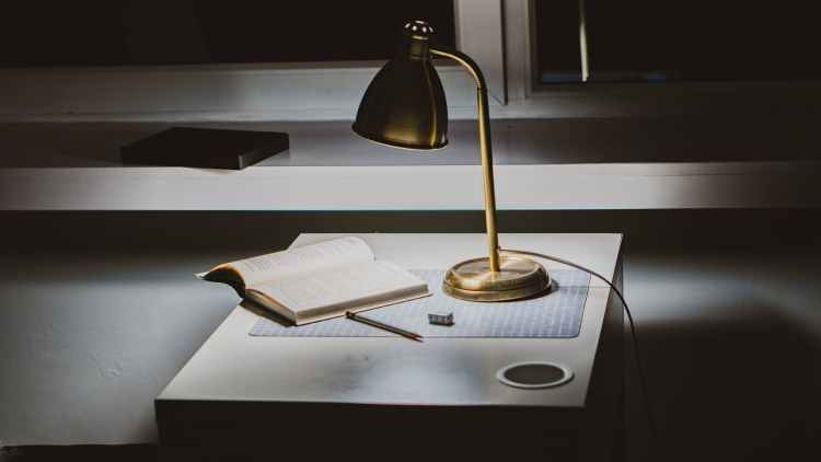 powered on gold desk lamp on desk with opened book